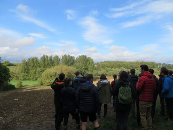 Students overlooking the Evenlode river across a ploughed field